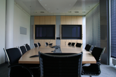 Large office with two flat screen televisions on the wall, a large beige office table and twelve black office chairs around it.