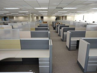 large office area with a bunch of cubicles along each side