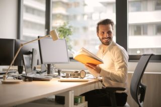 man at desk with a happy smile, looking at a folder