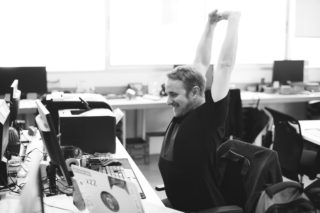 black and white photo of man stretching at this desk
