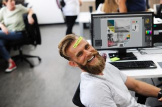 Man with beard smiling in an office enviroment