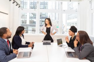 women at a long table in a large office for a meeting
