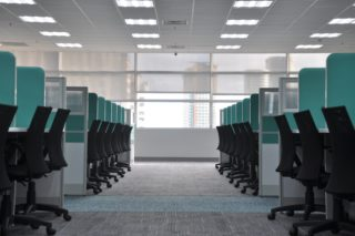 larger office space filled with cubicles on each side