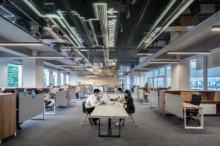 large office with high ceilings, a lot of cubicles and a table in the center with office workers sitting